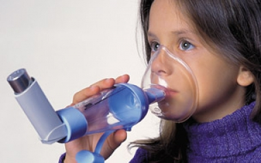 Image of a young girl using an inhaler spacer a
