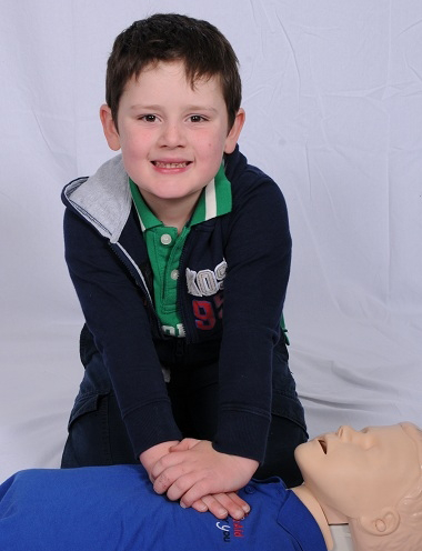 Image of a smiling young boy performing CPR on a dummy