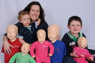 Image of mother with two young sons & resuscitation dummies