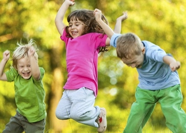 Image of 3 children jumps in the air with glee