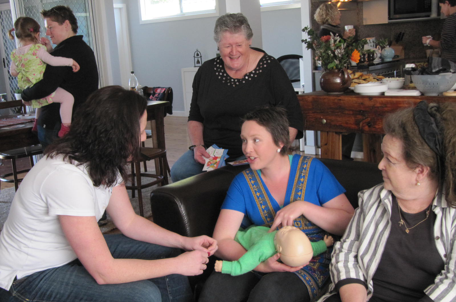 Image of first aid being taught at a baby shower, CPR on a baby