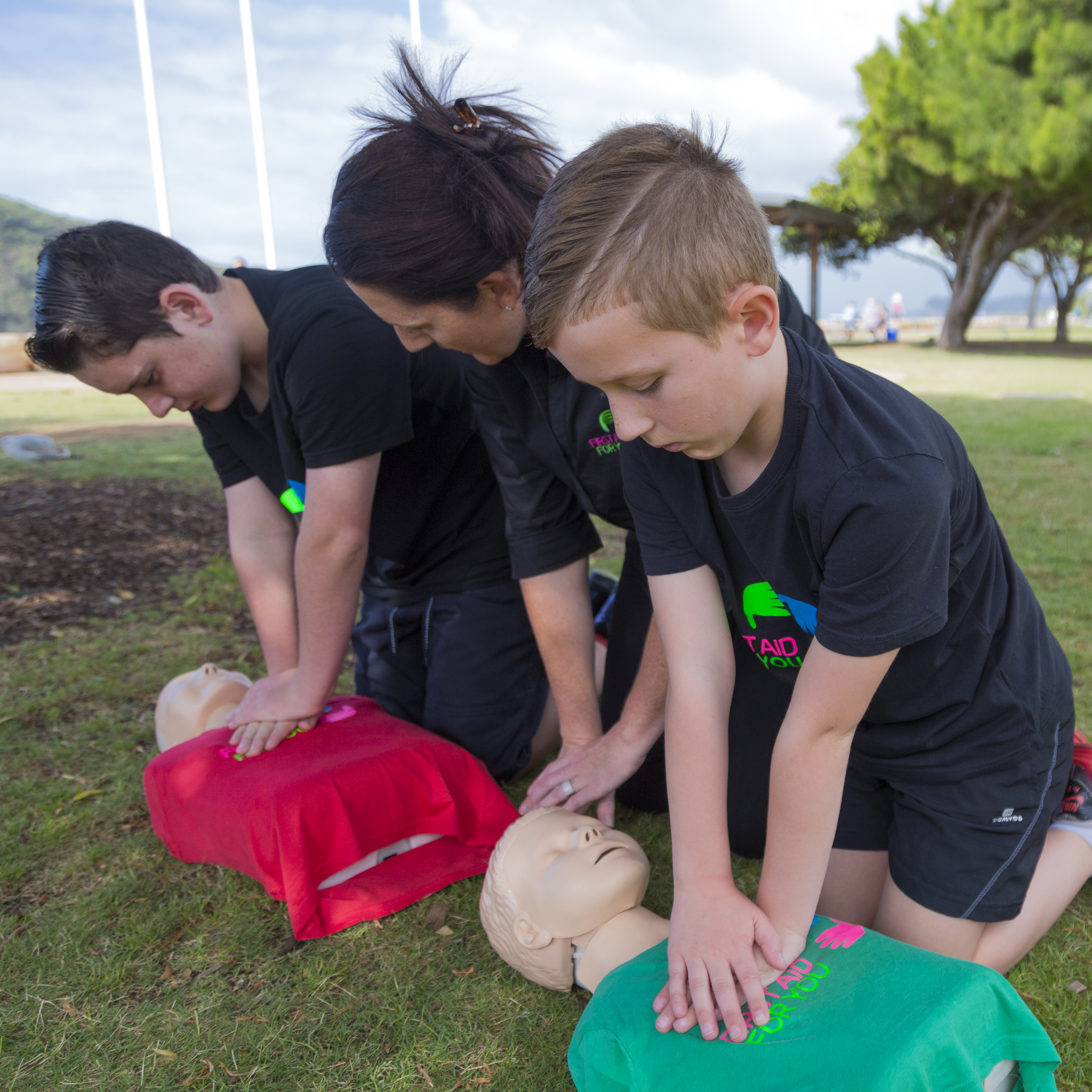 Mary Dawes of First Aid For You teaching 2 boys CPR