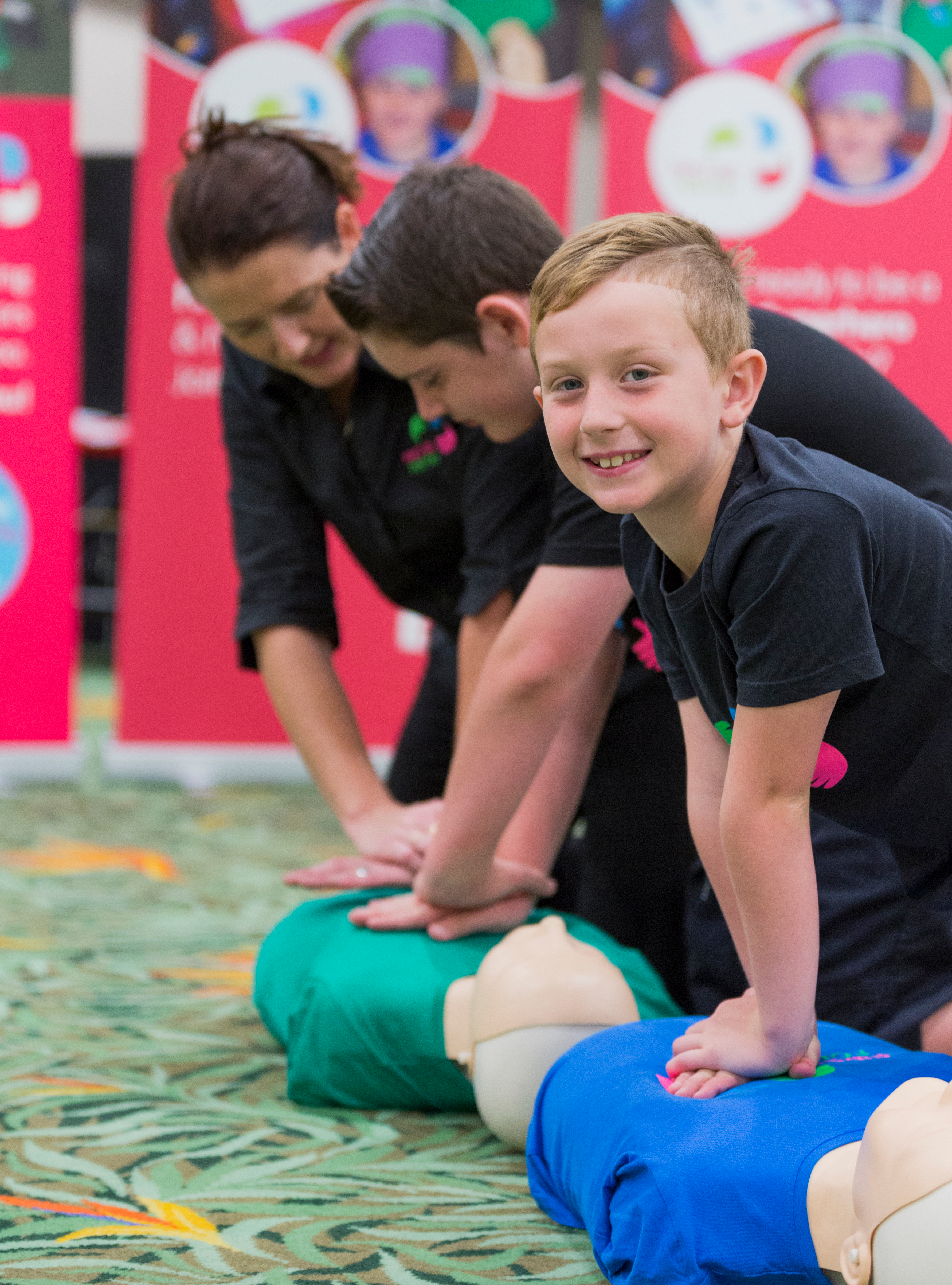 Image of smiling boy learning CPR on first aid mannequin with First Aid For You